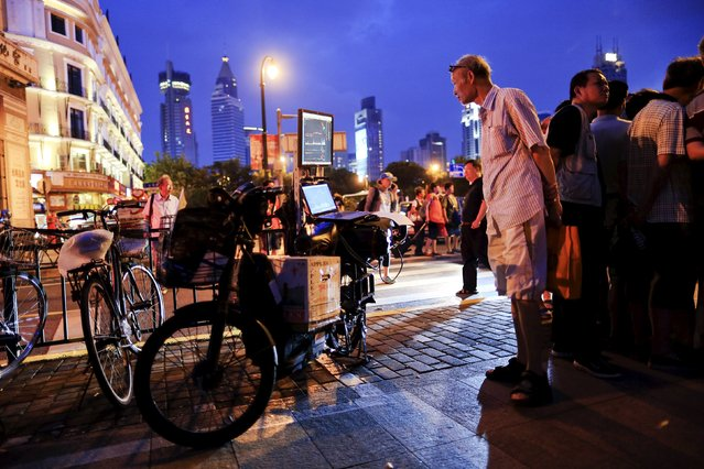 """Lv Hai looks at a screen displaying a stock analysis software, fixed to the back of an electric bicycle, during a """"street stock salon"""" in central Shanghai, China, September 5, 2015. For at least a decade, an area next to the People's Square temporarily has transformed itself into a """"street stock salon"""" during weekends, with investors from all over Shanghai coming to gather stock information and learn trading skills from others. A few businessmen also make use of the occasion to promote their stock analysis software. (Photo by Aly Song/Reuters)"""