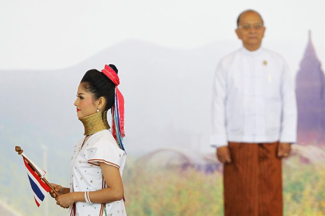 A girl wearing traditional clothes walks in front of Myanmar's President Thein Sein as he welcomes other heads of states before the East Asia Summit (EAS) plenary session during the ASEAN Summit in Naypyitaw November 13, 2014. (Photo by Soe Zeya Tun/Reuters)