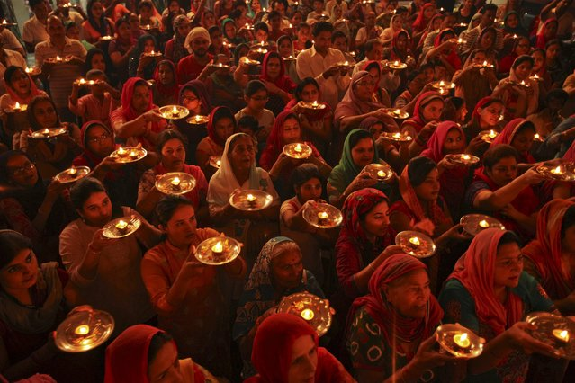 Hindu devotees with earthen oil lamps pray inside a temple during the Navratri festival in Chandigarh, India, October 13, 2015. The festival, which is held in honour of the Hindu goddess Durga, is celebrated over nine days. In Hindu mythology, Durga symbolises power and the triumph of good over evil. (Photo by Ajay Verma/Reuters)