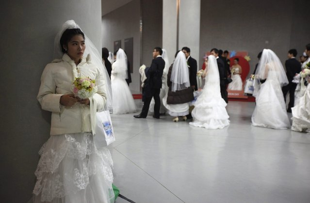 A bride waits for her groom during a mass wedding ceremony of the Unification Church at Cheongshim Peace World Centre in Gapyeong, about 60 km (37 miles) northeast of Seoul February 17, 2013. The Unification Church founded by evangelist reverend Moon Sun-myung in Seoul in 1954, performed its first mass wedding in 1961 with 33 couples. Approximately 3,500 couples attended the mass wedding on Sunday. (Photo by Kim Hong-Ji/Reuters)