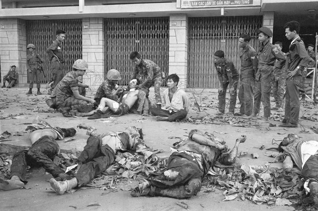 In this early 1968, file photo, South Vietnamese troops tend to wounded people as bodies line a Saigon street during the Tet Offensive. Early on the morning of January 31, 1968, as Vietnamese celebrated the Lunar New Year, or Tet as it is known locally, Communist forces launched a wave of coordinated surprise attacks across South Vietnam. The campaign, one of the largest of the Vietnam War, led to intense fighting and heavy casualties in cities and towns across the South. (Photo by Eddie Adams/AP Photo)