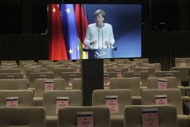 German Chancellor Angela Merkel, displayed on a screen, talks during an online press conference with European Commission President Ursula von der Leyen and European Council President Charles Michel following an EU-China virtual summit at the European Council building in Brussels, Monday, September 14, 2020. Michel, Merkel and Von der Leyen had talks in a videoconference with China's President Xi Jinping. (Photo by Yves Herman/Pool Photo via AP Photo)