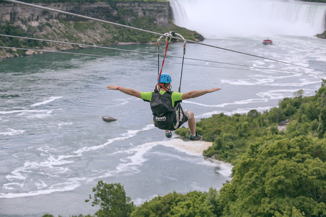 In this July 19, 2016 photo provided by WildPlay Ltd., a tourist suspended above the water from zip lines makes his way at speeds of up to 40 mph toward the the mist of the Horseshoe Falls, on the Ontario side of Niagara Falls. The overhead cables have evolved from a fun way to explore jungle canopies to trendy additions for long-established outdoor destinations. (Photo by Kien Tran/WildPlay Ltd. via AP Photo)