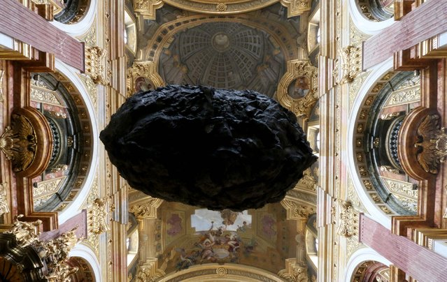 """A boulder plastic made of synthetic material called """"To be in Limbo"""" hangs from the ceiling of the 20 meter high Jesuit Church in Vienna, Austria, Tuesday, November 25, 2014. The eight meter high, hollow and 700 kilogram heavy sculpture from the artists group Steinbrener/Dempf and Huber is supposed to symbolize faith and its threatening moments. The installation will remain until April 19, 2015 and then move to a church in Hamburg, Germany. (Photo by Ronald Zak/AP Photo)"""