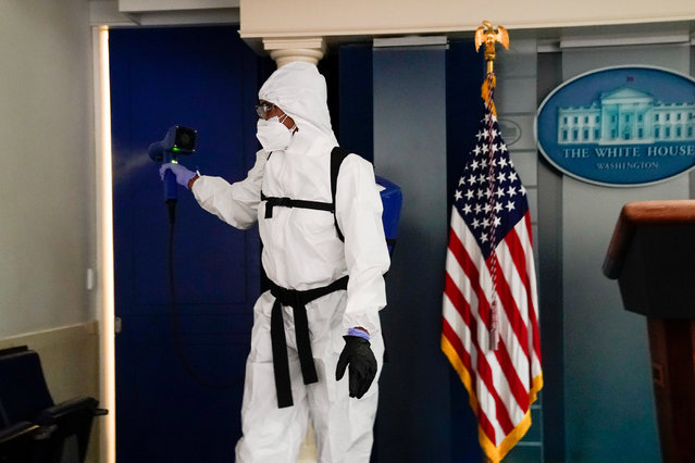 A member of the White House cleaning staff sprays the press briefing room the evening of U.S. President Donald Trump's return from Walter Reed Medical Center after contracting the coronavirus disease (COVID-19), in Washington, U.S., October 5, 2020. (Photo by Erin Scott/Reuters)