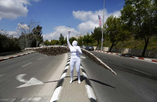 Reut Harel, a street performer, stands in a pose as she promotes the 2013 Jerusalem Science Festival March 18, 2013. The Jerusalem municipality and local museums are hosting a five-day festival focusing on developments in the science world. (Photo by Baz Ratner/Reuters)