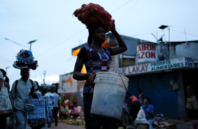 People carry their goods along a street market while Hurricane Matthew approaches in Port-au-Prince, Haiti, October 2, 2016. (Photo by Carlos Garcia Rawlins/Reuters)