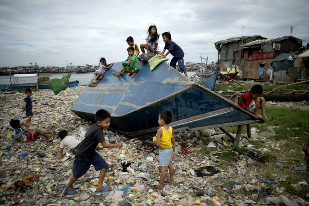 Children play on a boat in a shanty town at the port area in Manila on December 7, 2014 ahead of the arrival of typhoon hagupit. Shanties at the bay of Manila will be affected as typhoon hagupit will pass near Manila. Typhoon Hagupit tore apart homes and sent waves crashing through coastal communities across the eastern Philippines on December 7, creating more misery for millions following a barrage of deadly disasters. (Photo by Noel Celis/AFP Photo)