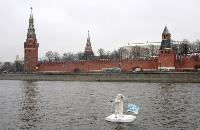 A greenpeace activist dressed as a polar bear sits on the wooden block of ice on the Moskva River in Moscow, Russia, protesting against plans of oil companies' drilling in the Arctic, on April 1, 2013. The activist was arrested by police, but is released on freedom later. (Photo by Liza Udilova/Greenpeace)
