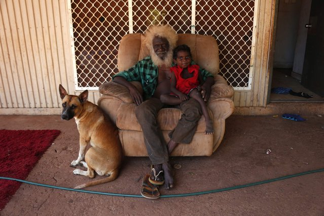 Robin Mildjingi and his grandson Gasier of the Yolngu people pose for a photograph as they sit out the front of their house in the Australian Aboriginal community of Ramingining located in East Arnhem Land November 21, 2014. (Photo by David Gray/Reuters)