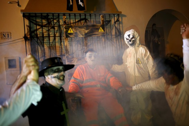 """People perform in the second edition of """"Noche del Terror"""" (Horror night) during Halloween celebrations in the neighborhood of Churriana, near Malaga, southern Spain, October 31, 2015. (Photo by Jon Nazca/Reuters)"""
