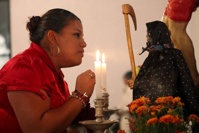 """A woman blows smoke from a cigarette towards a figurine of La Santa Muerte (Saint Death) at a shrine during Day of the Dead celebrations in Ciudad Juarez, Mexico, November 2, 2015. The saint is often depicted as a skeletal """"grim reaper"""" and followers leave offerings of tequila, rum, beer, cigarettes, cash, flowers and candy at altars adorned with rosaries and candles. (Photo by Jose Luis Gonzalez/Reuters)"""