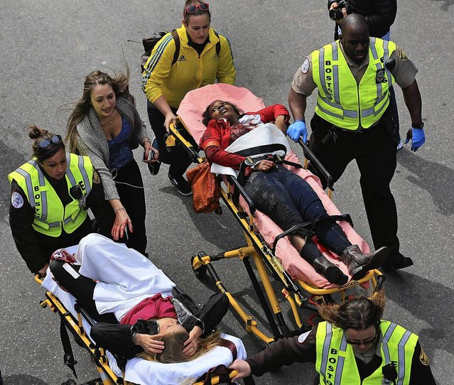 A person who was injured in an explosion near the finish line of the 117th Boston Marathon is taken away from the scene on a stretcher. (Photo by David L. Ryan/The Boston Globe)