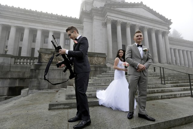 The best man in a wedding party, who all declined to be identified, stands near the bride and groom as he holds an AR-10 rifle he was handed while the party was having their pre-wedding portraits taken on the steps of the capitol before a rally nearby by gun-rights advocates to protest a new expanded gun background check law in Washington state Saturday, December 13, 2014, in Olympia, Wash. (Photo by Elaine Thompson/AP Photo)