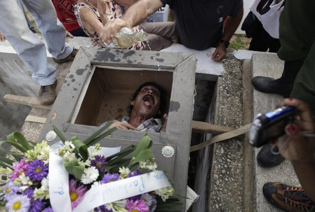 "In this February 5, 2014 file photo, Divaldo Aguiar, who plays the part of Pachencho, lies inside a mock coffin as villagers splash rum into Aguiar's mouth during the Burial of Pachencho celebration at a cemetery in Santiago de Las Vegas, Cuba. The bash kicked off with the slow procession to the local cemetery as pallbearers carried the coffin of ""Pachencho"". (Photo by Franklin Reyes/AP Photo)"