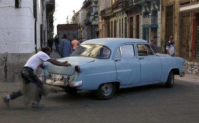 A man pushes a car in Havana December 19, 2014. (Photo by Enrique De La Osa/Reuters)