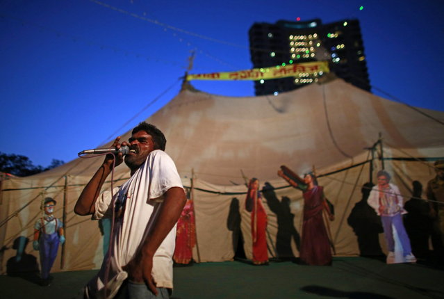 An employee of Anoop Touring Talkies, a travelling tent cinema company, speaks into a microphone to advertise a film in Mumbai April 23, 2013. (Photo by Danish Siddiqui/Reuters)