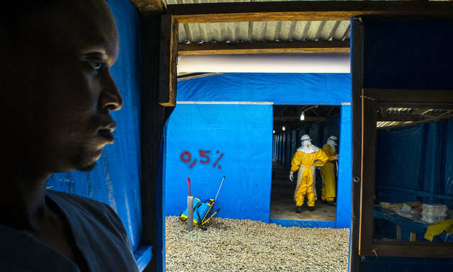 Moses Tarkulah stands by as colleagues enter the suspected Eloba case ward Bong County Ebola Treatment Unit, on Tuesday September 16, 2014.The newly opened 50 bed unit is managed by International Medical Corp, and was built by Save the Children. On its second day of operation to it has 3 new patients; one patient died Monday night. (Photo by Michel du Cille/The Washington Post)