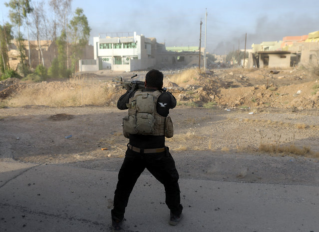 An Iraqi special forces soldier fires his rifle during clashes with Islamic States fighters in Bartella, east of Mosul, Iraq October 20, 2016. (Photo by Goran Tomasevic/Reuters)