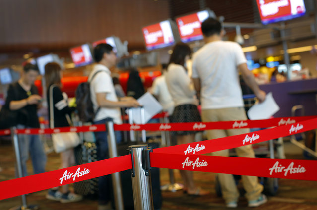 Passengers queue for their flights at the AirAsia check-in counter in Changi International Airport on Sunday, Dec. 28, 2014 in Singapore. (Photo by Wong Maye-E/AP Photo)