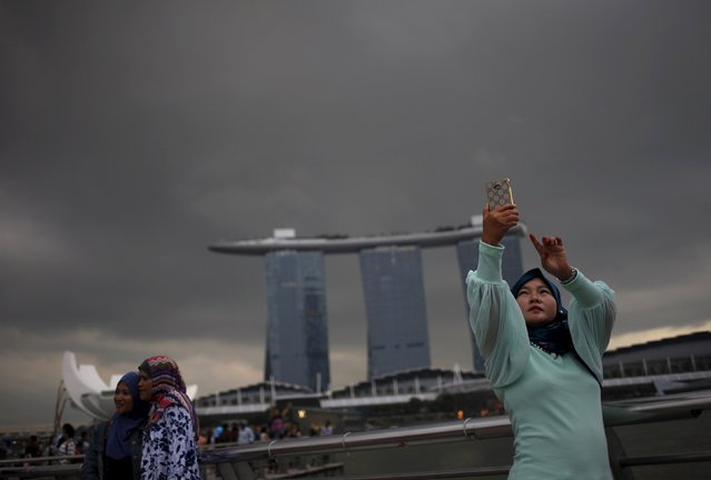 Indonesian tourists take photos at the Marina Bay in Singapore May 14, 2015. (Photo by Edgar Su/Reuters)