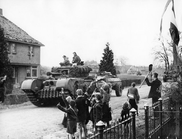Picture released on April 12, 1945 of Dutch civilians waving to the Canadian soldiers driving through a village of Netherlands, during the Second World War. (Photo by AFP Photo)