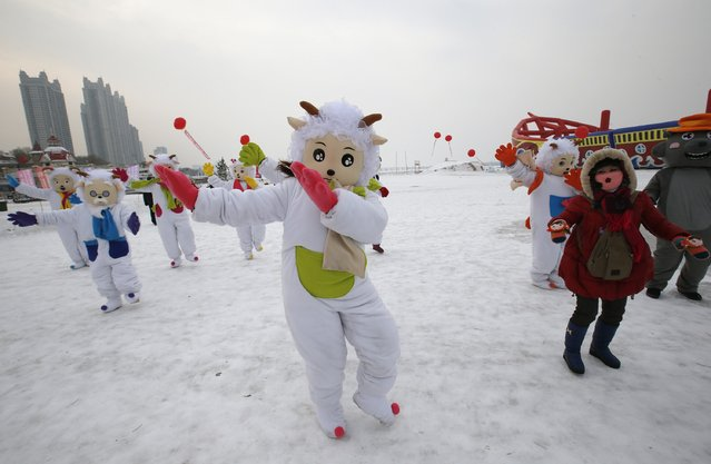 Dancers in costumes symbolizing sheep dance with visitors at an event to celebrate Harbin International Ice and Snow Sculpture Festival at the Songhua River in the northern city of Harbin, Heilongjiang province January 5, 2015. (Photo by Kim Kyung-Hoon/Reuters)