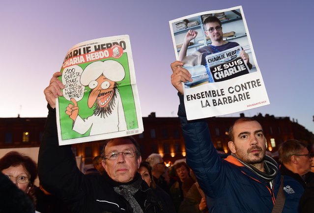 "People holds a Charlie Hebdo frontpage (L) and a picture of late French cartoonist Charb reading ""together against barbarism"" during a gathering in Toulouse on January 7, 2015, in solidarity for the victims of the attack by unknown gunmen on the offices of the satirical weekly, Charlie Hebdo. (Photo by Eric Cabanis/AFP Photo)"
