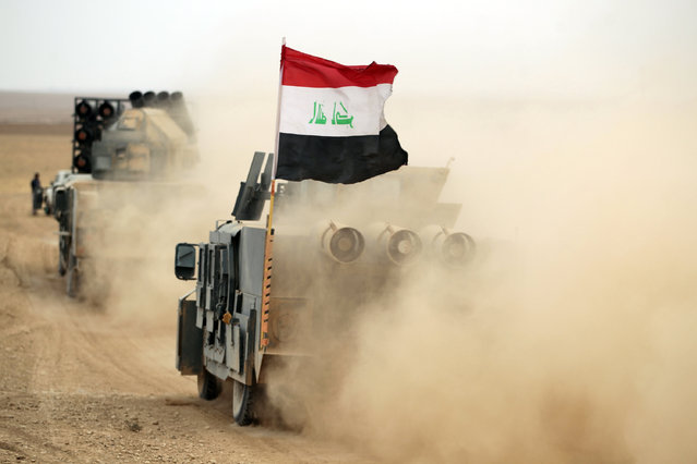 Iraqi forces drive their vehicles in the al-Shura area, south of Mosul, on October 28, 2016 during an operation to retake the main hub city from the Islamic State (IS) group jihadists. Jihadists have killed scores of people and taken tens of thousands to use as human shields in the Mosul area, the United Nations said, as Iraqi forces temporarily halted their advance on the city. (Photo by Ahmad Al-Rubaye/AFP Photo)