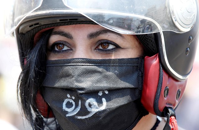 "A demonstrator, wearing a mask as a preventive measure against the spread of coronavirus disease (COVID-19), attends a protest against the growing economic hardship and to mark Labour Day in Beirut, Lebanon on May 1, 2020. The word ""Revolution"" reads on the mask. (Photo by Mohamed Azakir/Reuters)"