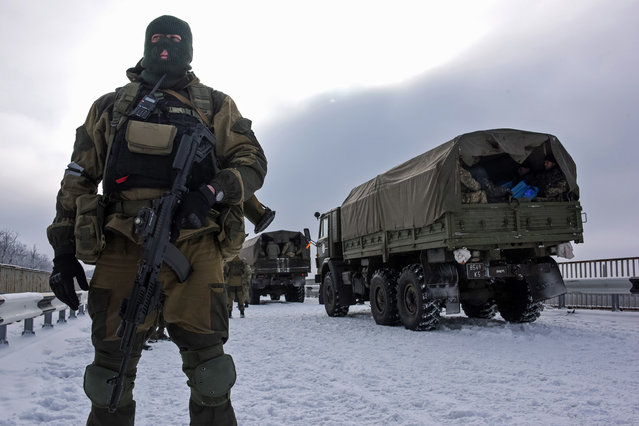 A pro-Russian rebel guards the road near the airport of Donetsk, with Ukrainian military vehicles at rear, Eastern Ukraine, Tuesday, January 6, 2015. Ukrainian soldiers took up duties Tuesday at the Donetsk Airport, scene of some of the fiercest fighting in eastern Ukraine. The 50 soldiers in a convoy of four trucks were provided safe passage to the airport by rebel forces, who gave them gifts in celebration of Orthodox Christmas. (Photo by Mstyslav Chernov/AP Photo)