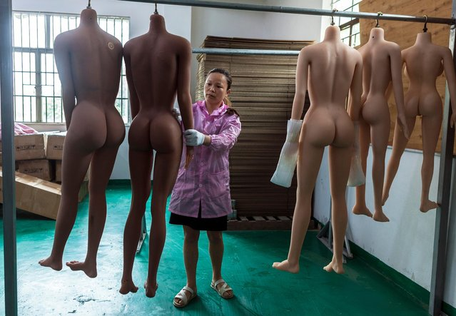 A worker hangs dolls' bodies to dry and checks them in s*x dolls factory in Dongguan, Guandong Province, China, 24 April 2018. (Photo by Aleksandar Plavevski/EPA/EFE)