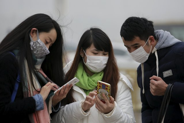 People wearing protective masks check their phones at the Tiananmen Gate on an extremely polluted day as hazardous, choking smog continues to blanket Beijing, China December 1, 2015. (Photo by Damir Sagolj/Reuters)