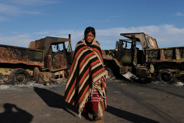 A woman from the Navaho tribe stands in front of two trucks on a bridge during a protest of the Dakota Access pipeline on the Standing Rock Indian Reservation near Cannon Ball, North Dakota November 6, 2016. (Photo by Stephanie Keith/Reuters)