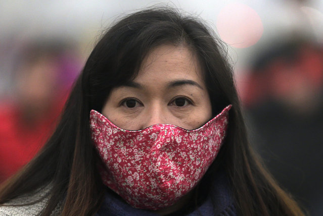 In this December 1, 2015 photo, a woman wears a mask to protect herself from pollutants near Tiananmen Gate on a heavily polluted day in Beijing. (Photo by Andy Wong/AP Photo)