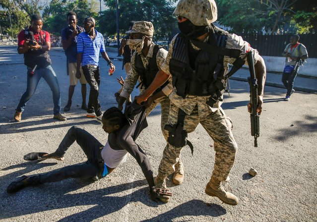 Police officers detain a man during protests against Haiti's President Jovenel Moise in Port-au-Prince, Haiti on February 8, 2021. (Photo by Jeanty Junior Augustin/Reuters)