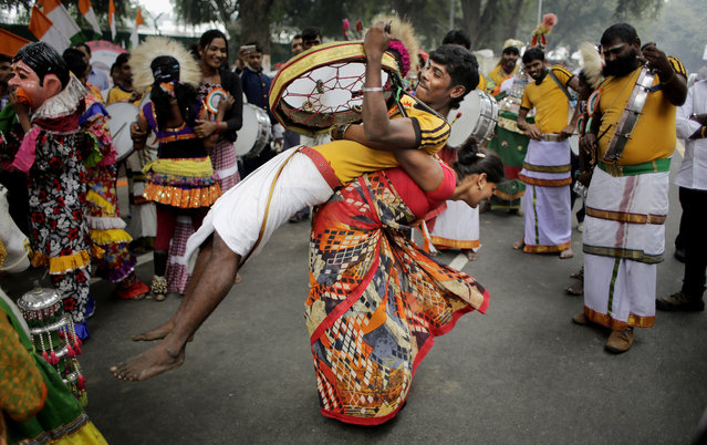 Tribal artists and supporters from the southern Indian state of Karnataka dance outside the residence of Congress Party President Sonia Gandhi during her birthday celebrations in New Delhi, India, Wednesday, December 9, 2015. The Italian-born Gandhi is the widow of former Prime Minister Rajiv Gandhi and has led the Congress party since 1998. (Photo by Altaf Qadri/AP Photo)