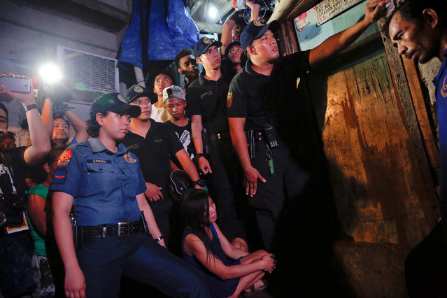 Funeral parlour workers, policemen, reporters and the relatives of a person who was killed, wait for investigation to be done outside a house in Manila, Philippines early November 1, 2016. (Photo by Damir Sagolj/Reuters)