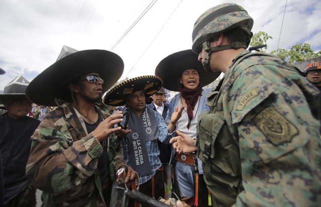 Indigenous men talk with a soldier who stands guard to prevent possible clashes between dance groups from different communities celebrating the Sun Festival in the main plaza of Cotacachi, Ecuador, Sunday, June 24, 2018. (Photo by Dolores Ochoa/AP Photo)