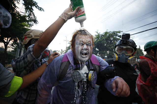 A pro-democracy protester has his face rinsed as police fire tear gas and water cannon during a demonstration against a charter amendment at Parliament in Bangkok, Thailand, 17 November 2020. Thai Members of Parliament are meeting on 17 and 18 November to vote on plans for amending the nation's constitution. The vote comes after week of pro-democracy and monarchical reform protests. (Photo by Diego Azubel/EPA/EFE)
