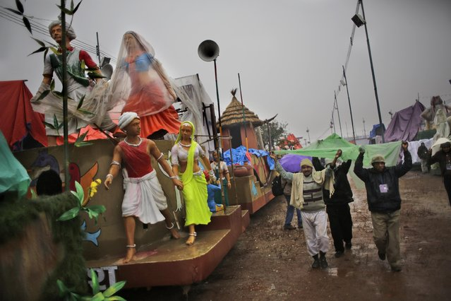 Workers cover themselves from rain as they walk past tableaux during a media preview displaying a glimpse of culture of different parts of India, in New Delhi, India, Thursday, January 22, 2015. (Photo by Altaf Qadri/AP Photo)