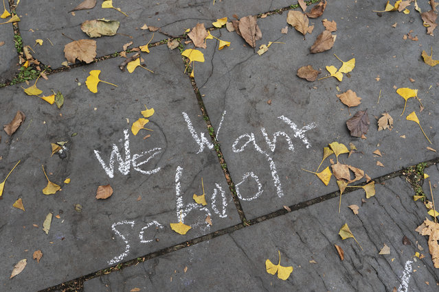A student's graffiti is written on a sidewalk in front of New York's City Hall during a protest by parents and students opposing the closing of schools, Thursday, November 19, 2020. Mayor Bill de Blasio announced Wednesday that the nation's largest school system will move to remote learning only as the city tries to tamp down a growing number of coronavirus cases. (Photo by Mark Lennihan/AP Photo)