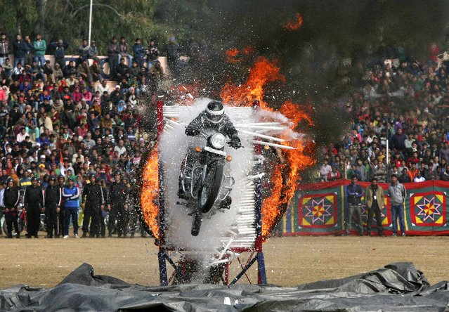 An Indian policeman performs a stunt on his motorcycle during the Republic Day parade in Jammu January 26, 2015. (Photo by Mukesh Gupta/Reuters)