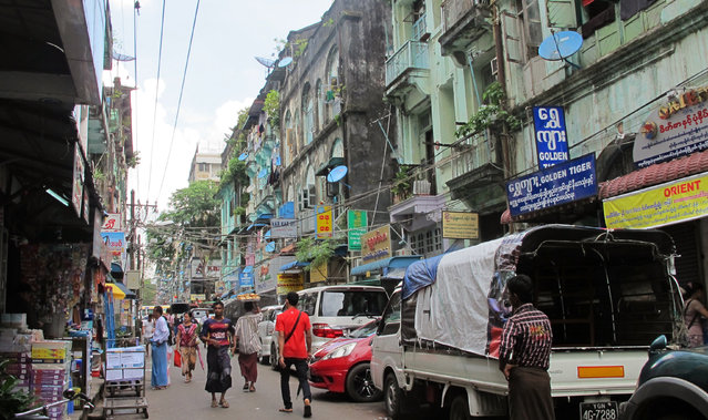In this October 3, 2016 photo, people walk in a downtown shopping street lined with old colonial buildings used as shops, restaurants and houses in Yangon, Myanmar. (Photo by Elaine Kurtenbach/AP Photo)