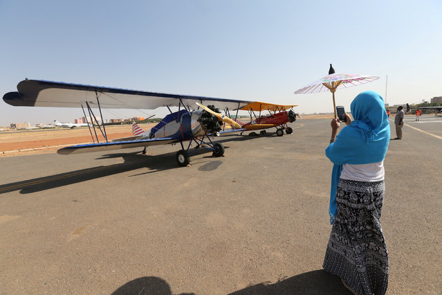 A woman takes pictures of a biplane after 18 biplanes landed at Khartoum Airport in Sudan during a tour across Africa, November 20, 2016. (Photo by Mohamed Nureldin Abdallah/Reuters)