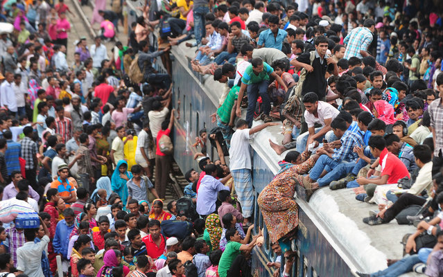 Passengers climb to board an overcrowded train at a railway station in Dhaka August 8, 2013. (Photo by Munir uz Zaman/AFP Photo)