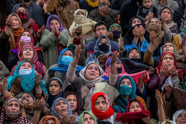 Kashmiri Muslim women pray as the head priest displays a relic at the Hazratbal shrine on the occasion of Mehraj-u-Alam, believed to mark the ascension of Prophet Muhammad to heaven, in Srinagar, Indian controlled Kashmir, Friday, March 12, 2021. Thousands of Kashmiri Muslims gathered at the Hazratbal shrine, which houses a relic believed to be a hair from the beard of Islam's Prophet Muhammad. (Photo by Dar Yasin/AP Photo)