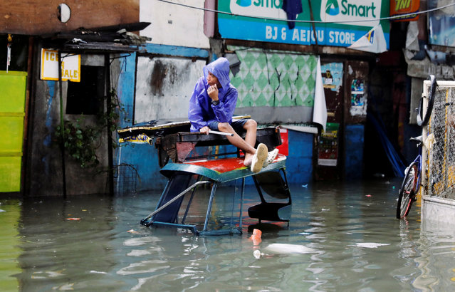 A resident rests on top of a pedicab along a flooded street caused by the monsoon rains and Tropical Storm Son-Tinh in Quezon city, Metro Manila, in Philippines on July 17, 2018. (Photo by Erik De Castro/Reuters)