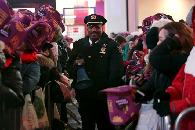 A police officer walks between revelers during New Year celebrations in Times Square in the Manhattan borough of New York December 31, 2015. (Photo by Andrew Kelly/Reuters)