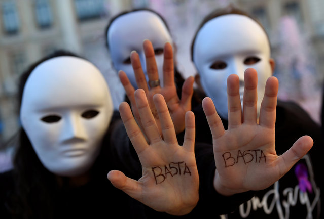 "Gender studies students wearing masks pose with the word ""Enough"" written on their hands during a performance to commemorate victims of gender violence, during the U.N. International Day for the Elimination of Violence against Women, in Oviedo, Spain November 25, 2016. (Photo by Eloy Alonso/Reuters)"